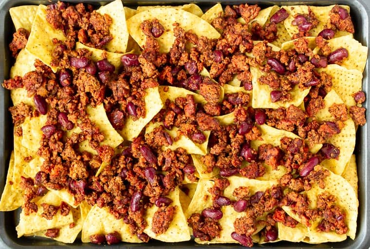Tortilla chips on a sheet pan topped with vegetarian chili.