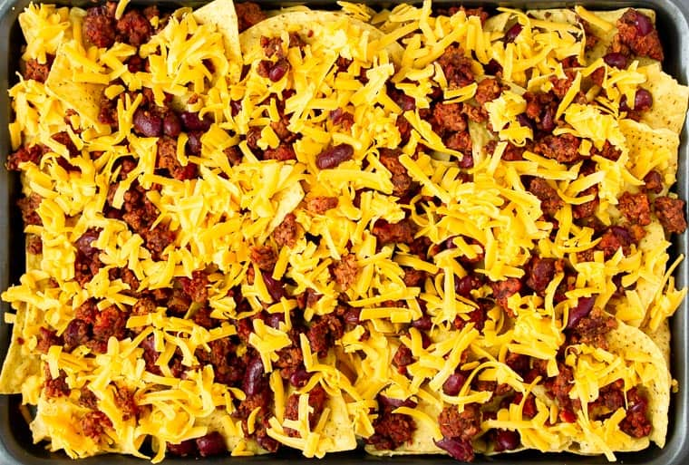 Tortilla chips on a sheet pan topped with vegetarian chili and cheese