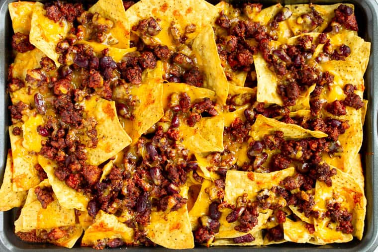 Baked tortilla chips on a sheet pan topped with vegetarian chili and melted cheese