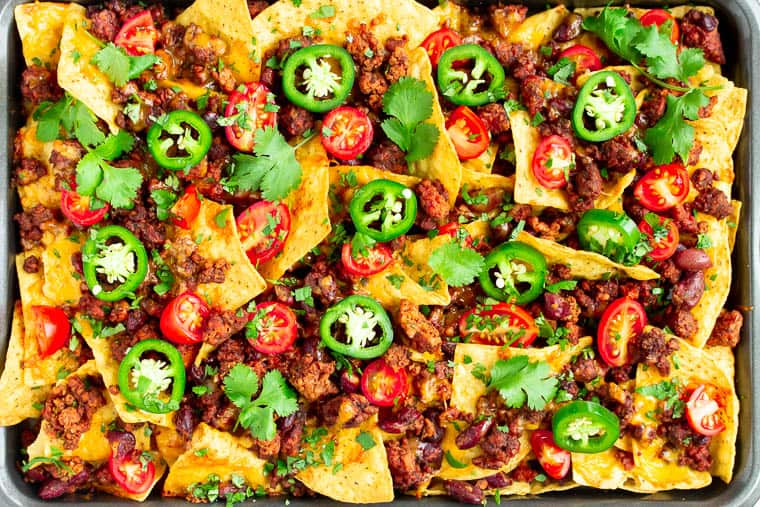 Sheet Pan Vegetarian Nachos topped with tomatoes, jalapenos, and cilantro
