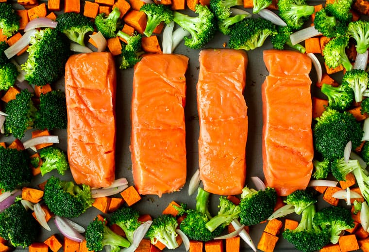 Salmon, broccoli, sweet potatoes. and shallots spread out on a gray sheet pan