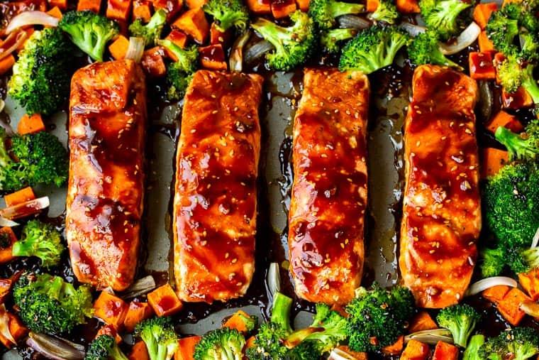 Baked Teriyaki Salmon with broccoli and sweet potatoes on a gray baking sheet
