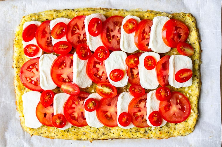 A pizza crust topped with layers of mozzarella cheese and tomatoes
