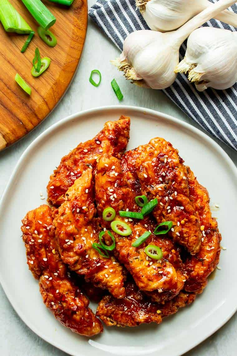 Overhead of Honey Garlic Chicken Tenders on a white plate with a cutting board, green onions, garlic bulbs, and a blue and white napkin in the background