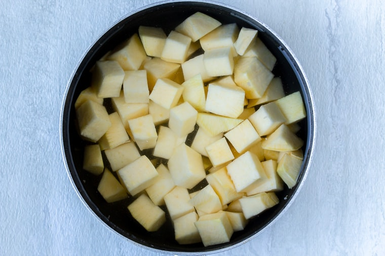 Cubes of rutabaga in a black saucepan over water over a white background