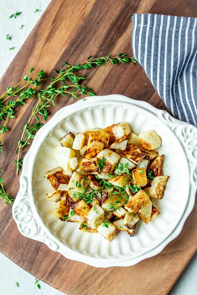 Overhead of roasted turnips in a white bowl over a wood cutting board with fresh thyme and a blue and white napkin in the background