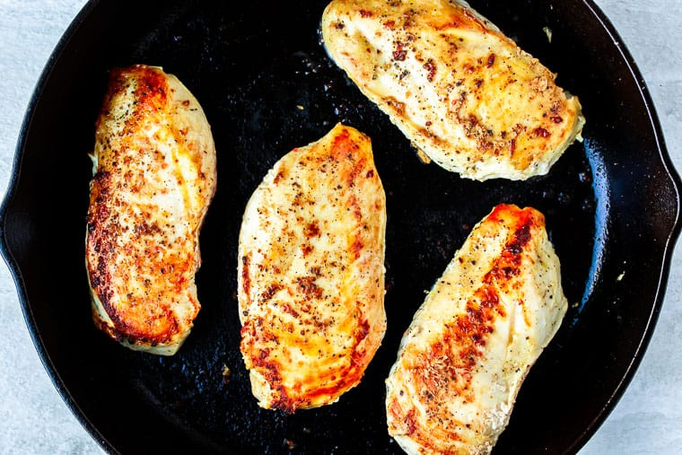 4 Chicken breasts cooking in a cast iron skillet over a white background