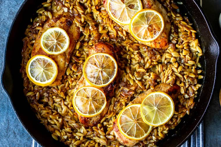 Baked Lemon Garlic Chicken with Orzo Pasta in a cast iron skillet on a blue and white striped towel over a blue background