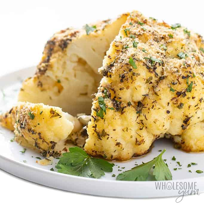 A roasted head of cauliflower on a white plate