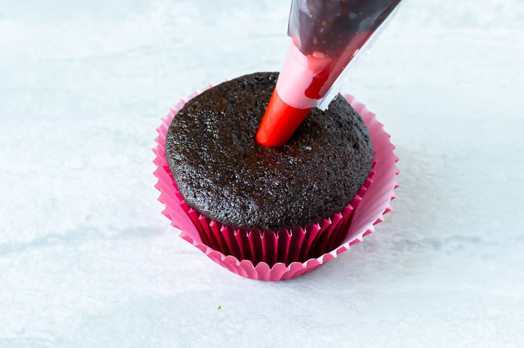 Raspberry jam being piped into the center of a chocolate cupcake over a white background