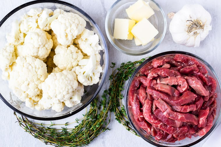 Ingredients for garlic butter steak bites in glass bowls over a white background