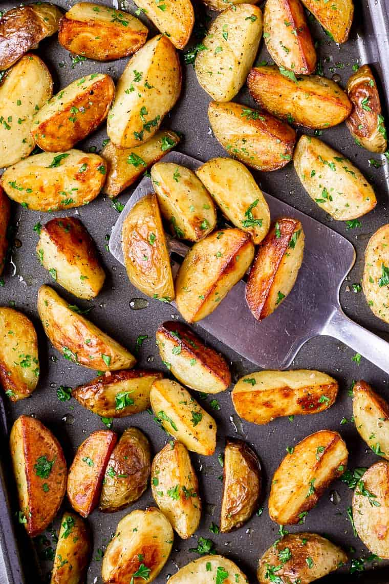 Close up of Oven Roasted Potato Wedges on a baking tray with a metal spatula scooping some up