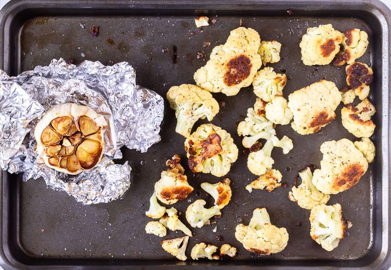 Roasted garlic and roasted cauliflower on separate sides of a baking sheet