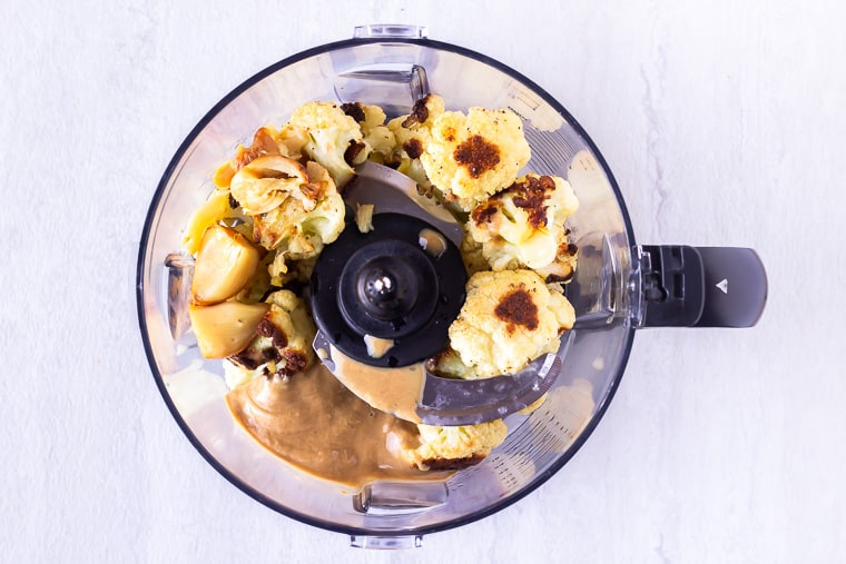 Roasted cauliflower, roasted garlic, lemon juice, and tahini in a food processor over a white background