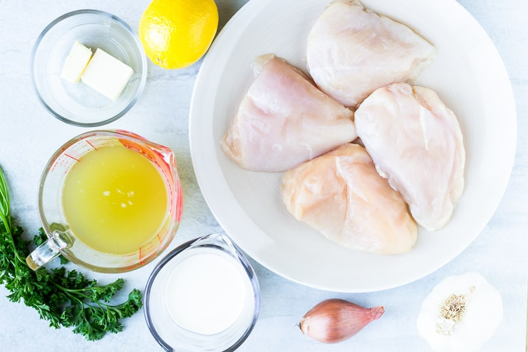 Ingredients needed to make Lemon Garlic Chicken sitting out over a white background