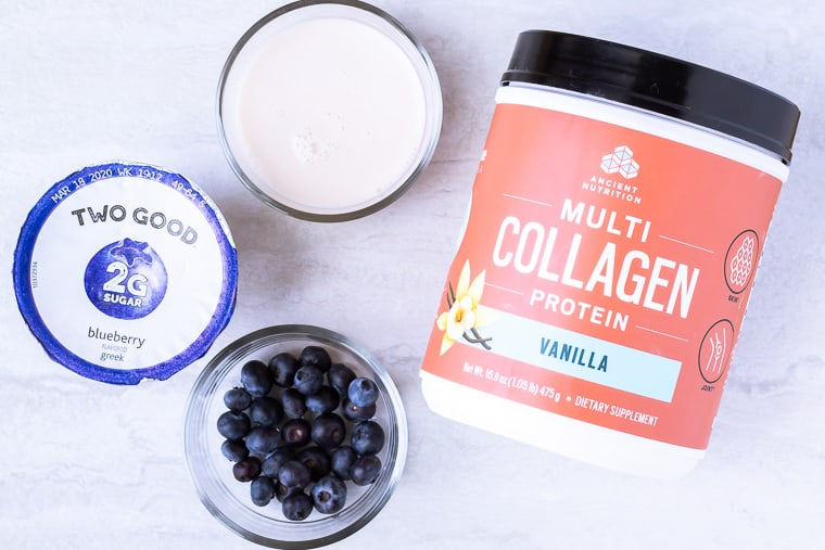 Ingredients needed to make a keto blueberry smoothie on a white background