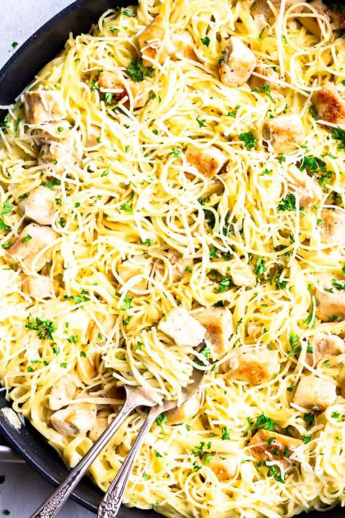 close up of garlic chicken pasta in a skillet with some wrapped around a fork with a spoon under it