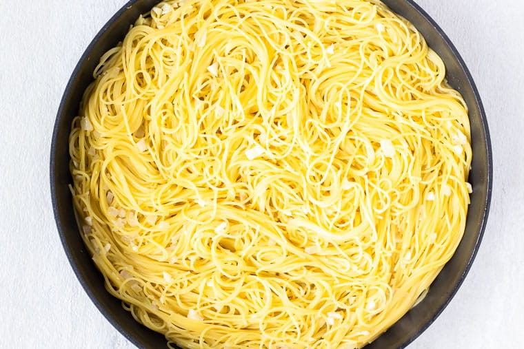 Cooked angel hair pasta in a skillet over a white background