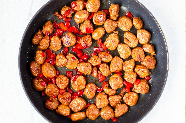 Sausage sliced and diced red pepper cooking in a black skillet over a white background