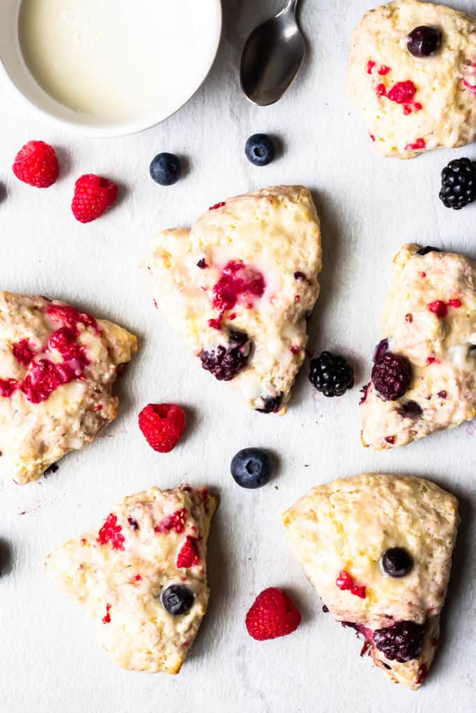 Overhead of 6 berry scones on a white background with fresh berries scattered around them, a small white bowl of glaze and a spoon