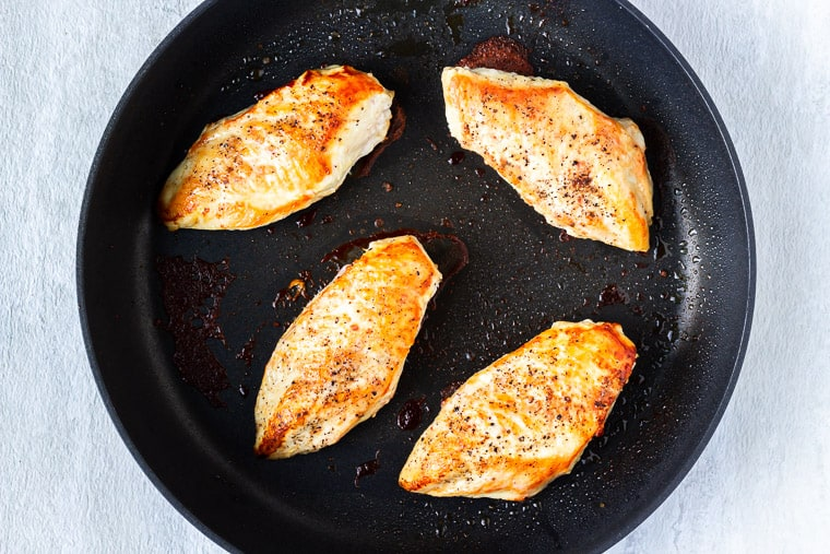4 pan-seared chicken breasts in a large black skillet over a white background