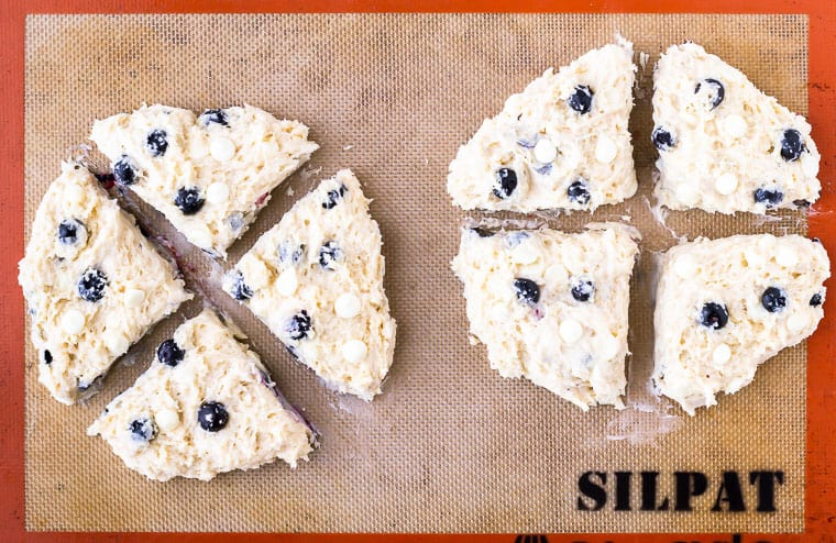 Blueberry scones dough divided into 2 rounds and cut into 4 triangles each