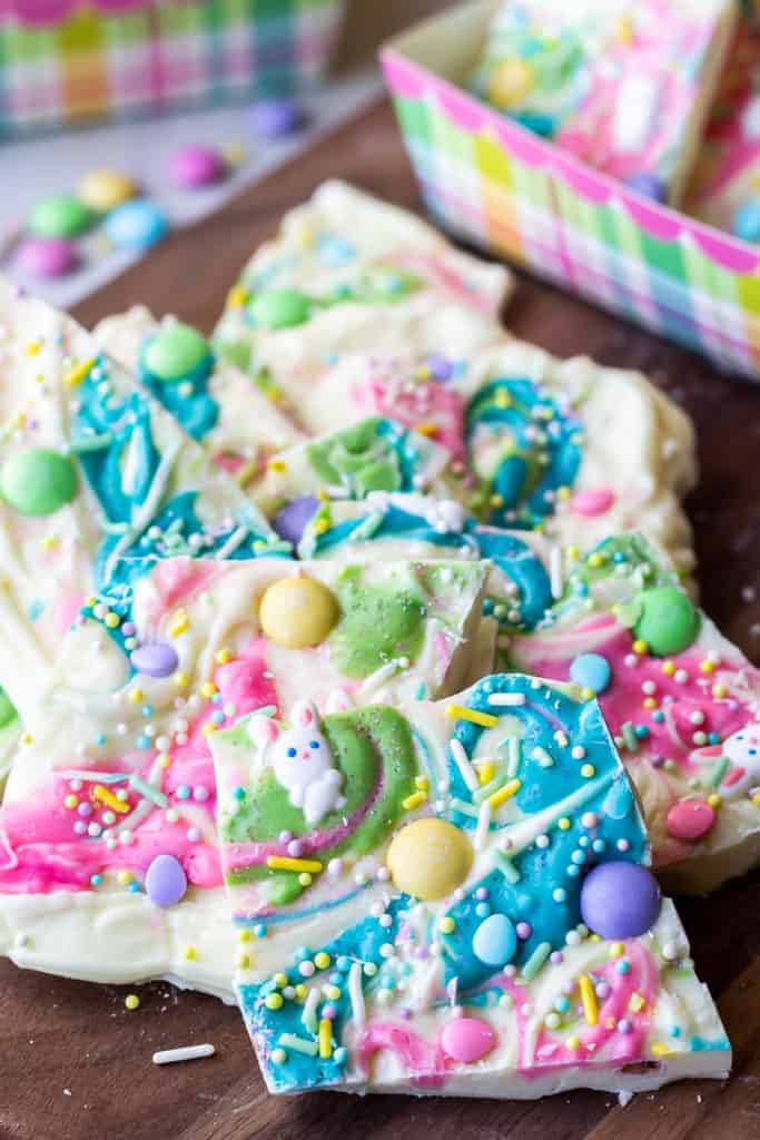 White chocolate easter bark broke into pieces on a wood board with easter boxes filled with more bark and loose candy and sprinkles in the background