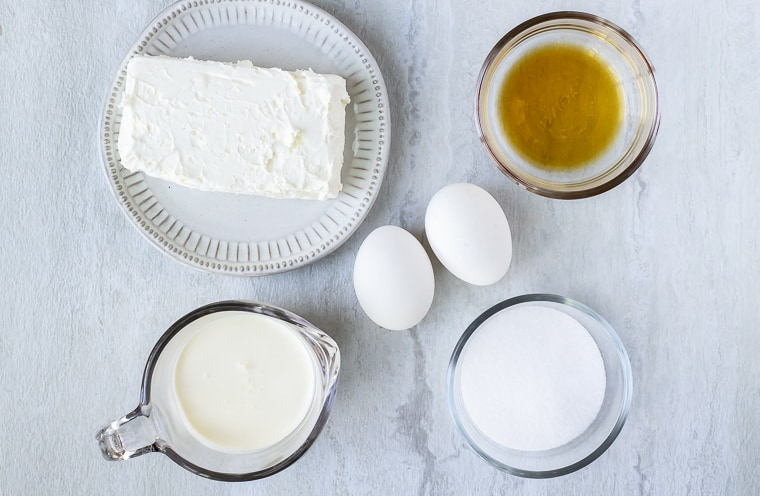 Ingredients for a crustless cheesecake in glass bowls on a white background
