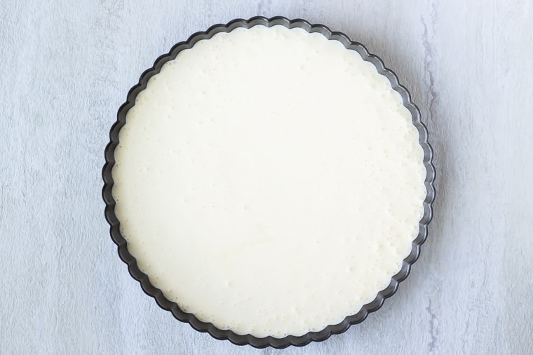 Cheesecake batter in a tart pan on a white background