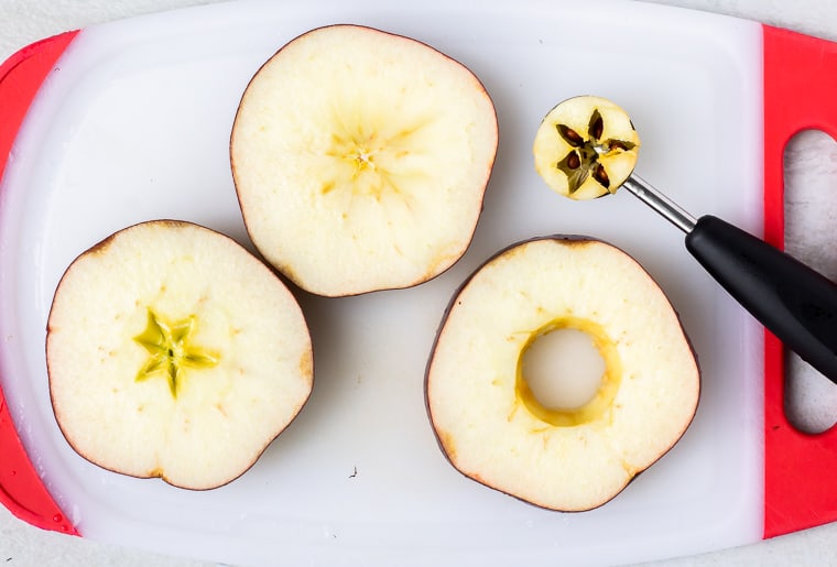 3 apple rounds with the core and seeds scooped out of one with a melon baller sitting off to the side on a white and red cutting board