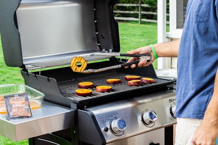 A person holding up a grilled apple slice over the grill with more slices still cooking on it. There is grass, a part of a wood fence, and a packet of seasoning in the background