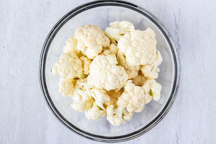 cauliflower florets in a glass bowl on a white background