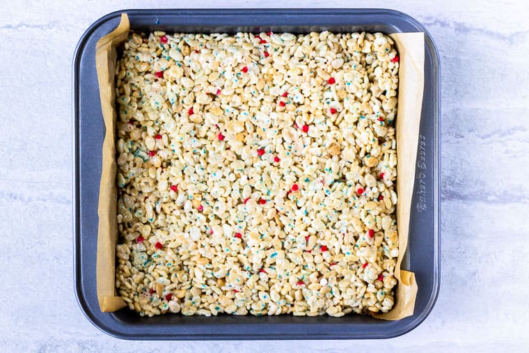 Rice krispies pressed into a square baking pan over a white background