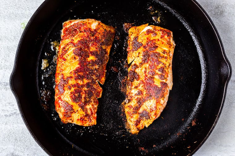 2 blackened cod fillets in a black cast iron pan over a white background