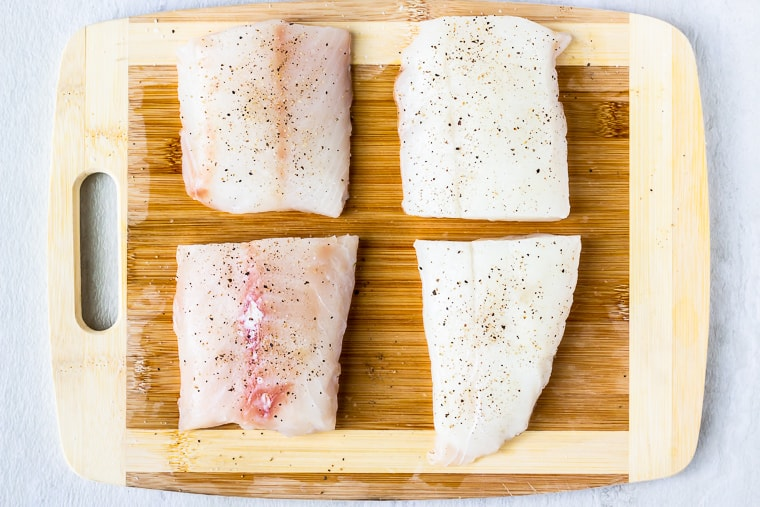 4 cod fillets on a wood cutting board with salt and pepper on them