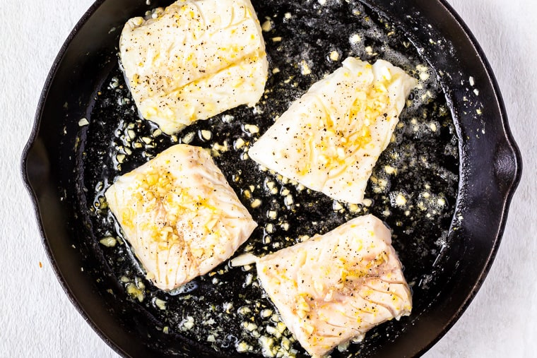 4 Cod fillets in lemon garlic butter sauce in a cast iron skillet over a white background