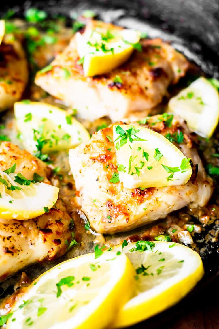 Close up of 2 cod fillets in a cast iron skillet with pieces of lemon, lemon slices, and parsley on them.
