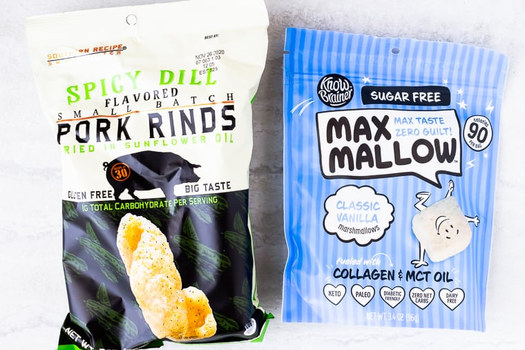 A bag of pork rinds and a bag of sugar free marshmallows on a white background