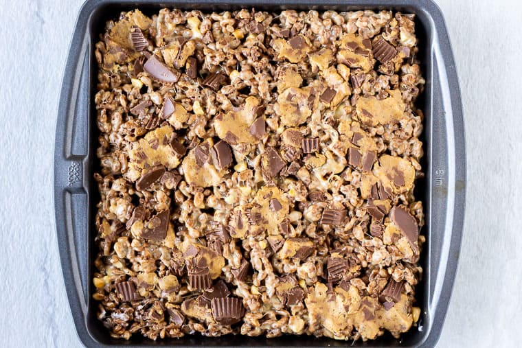 Cocoa Rice Krispies Treats with chopped Reese's Peanut Butter Cups pressed into the top in a square baking dish over a white background