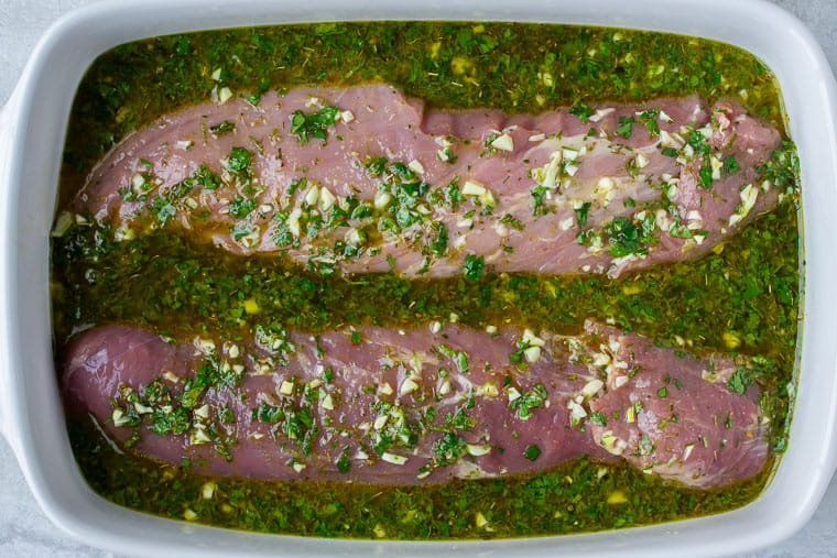 Pork Tenderloin Marinating in Cuban Marinade in a white baking dish