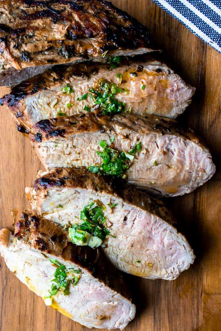 Cuban Pork Tenderloin sliced on a wood serving board