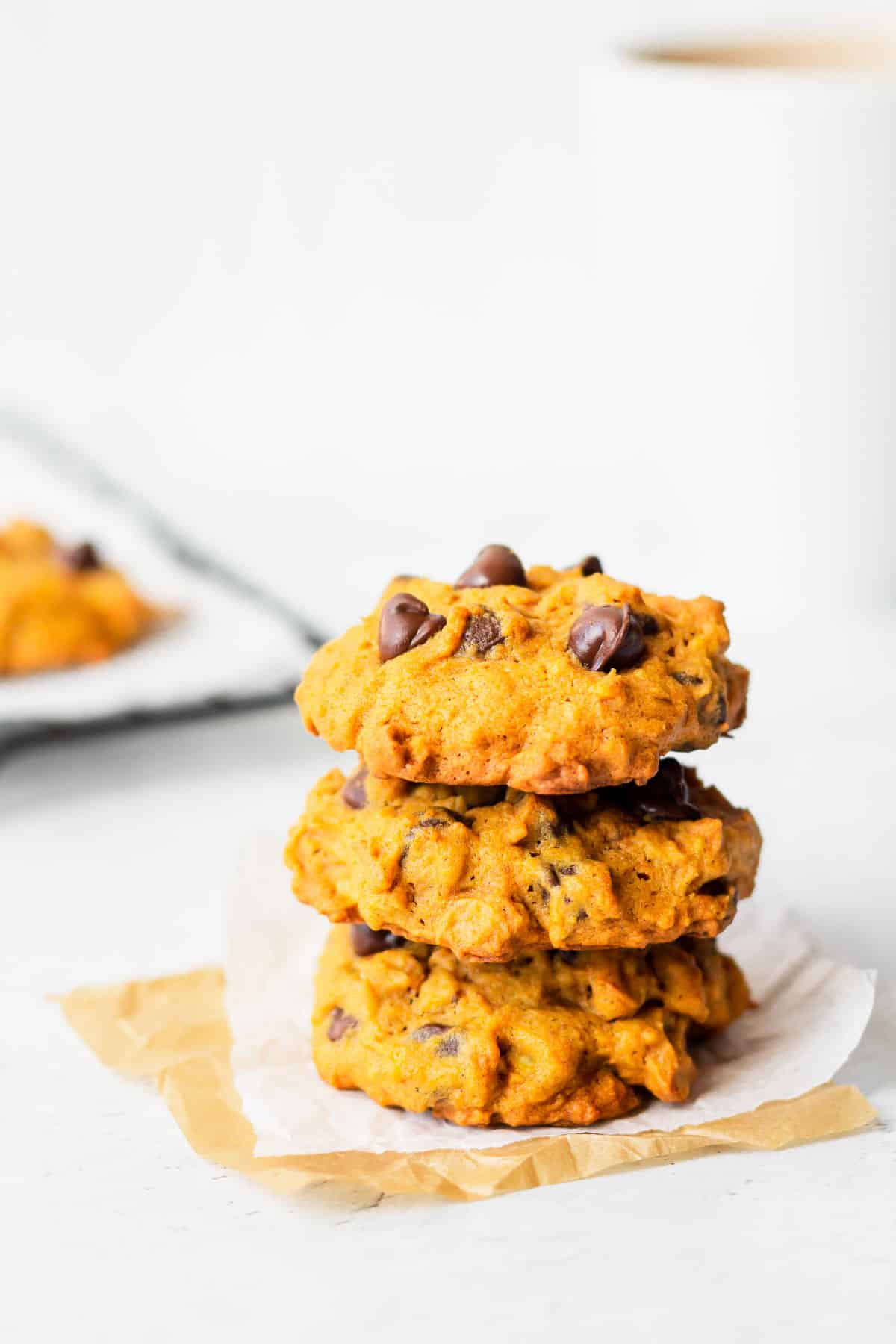 3 Pumpkin chocolate chip cookies stacked on top of each other with a mug and cooling rack with more cookies on it in the background