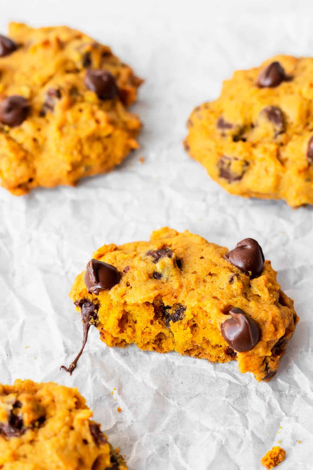 Close up of pumpkin chocolate chip cookies with one broke in half to show thick, soft texture