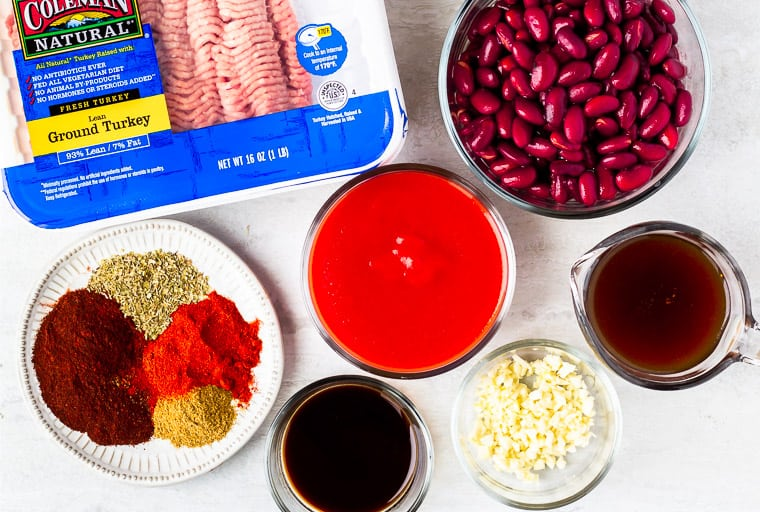 Ingredients needs to make instant pot turkey chili in glass bowls or plates over a white background