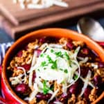 Instant pot turkey chili in a red crock style bowl with orange trim and a cutting board with a block and grated cheese with a blue and white striped towel over a blue gray backdrop
