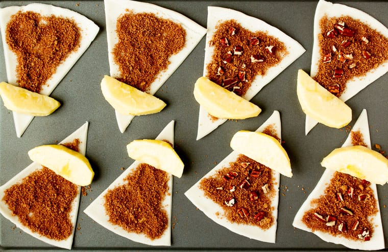 Apple slices placed on cinnamon sugar coated pie crust triangles