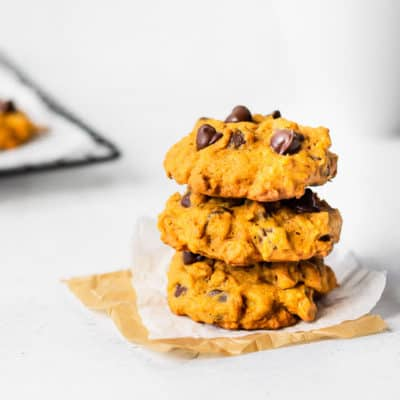 3 pumpkin chocolate chip cookies stacked on top of each other with part of a cooling rack and a mug in the background