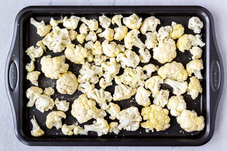 Raw cauliflower florets on a baking sheet over a white background
