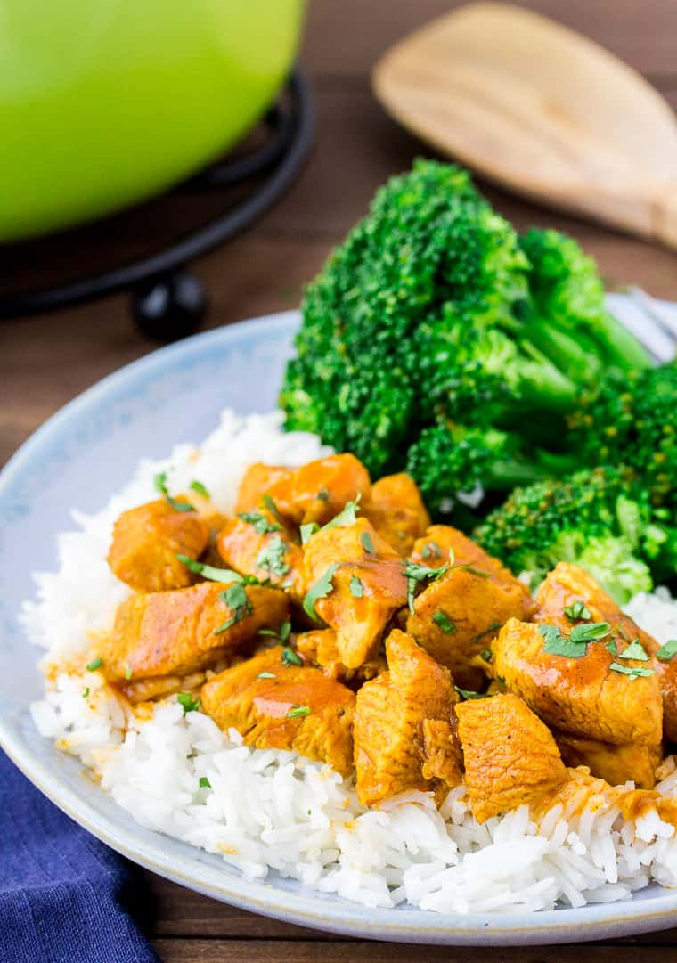 Coconut Curry Chicken over Rice with Broccoli. A Green pot and wood spoon in the background