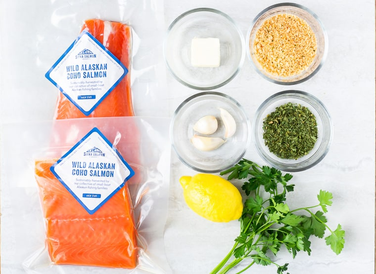 Ingredients needed to make lemon garlic salmon on a white background